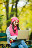 Cute woman with laptop in the autumn park. Stock Photography