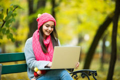 Cute woman with laptop in the autumn park. Stock Images