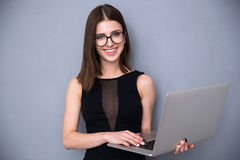 Cute woman with laptop standing over gray background royalty free stock image