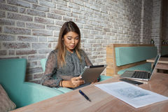 Cute woman lawyer is using digital table,. Female financier is reading financial news in internet via touch pad during work break in modern cafe Royalty Free Stock Photography