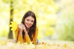 Cute woman laying in autumn park Stock Image