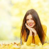 Cute woman laying in autumn park Stock Photo
