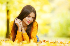 Cute woman laying in autumn park Stock Photos