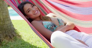 Cute woman laying back in hammock stock video footage