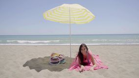 Cute woman laying down on beach blanket. Single cute woman laying down with chin resting on hand while on beach blanket next to bag with ocean in horizon stock video