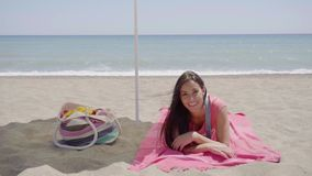 Cute woman laying down on beach blanket. Single cute woman laying down with chin resting on hand while on beach blanket next to bag with ocean in horizon stock footage