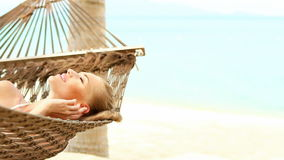 Cute woman laying on hammock. Cute woman lying on hammock on tropical beach stock video