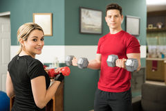 Cute woman lifting weights with her boyfriend Royalty Free Stock Photography