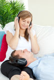 Cute woman listening to music with her boyfriend Royalty Free Stock Photos