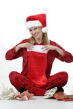 Cute woman looking in Christmas stocking Royalty Free Stock Photography