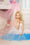 Cute woman looks like a doll in a sweet interior. Young pretty s Royalty Free Stock Images