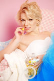Cute woman looks like a doll in a sweet interior. Young pretty s Stock Photos