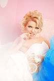 Cute woman looks like a doll in a sweet interior. Young pretty s Royalty Free Stock Photography