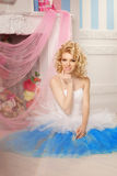 Cute woman looks like a doll in a sweet interior. Young pretty s Royalty Free Stock Image
