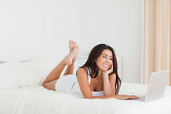 Cute woman lying on bed with crossed legs Stock Photography