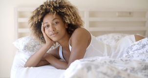 Cute woman lying on bed at home in bedroom Stock Photos