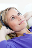 Cute woman lying down on sofa listening music Stock Photography