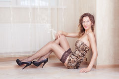 Cute woman lying on the floor smoking a cigar wearing stockings Stock Image