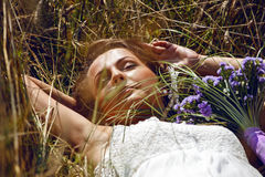 Cute woman lying on the grass. Beautiful bride lying on the grass Royalty Free Stock Images