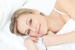 Cute woman lying on her bed Stock Photos