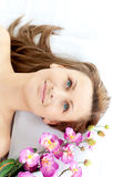 Cute woman lying on a massage table with flowers Stock Image