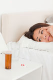 Cute woman lying under sheet having headache Stock Photography