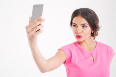 Cute woman making duck face and taking selfie using smartphone Royalty Free Stock Image