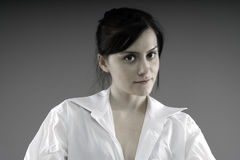 Cute woman in a man's white shirt. On a gray background Stock Photo