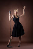 Cute woman with microphone on dark background Stock Photo