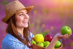Cute woman offers an apple. Closeup portrait of cheerful cute woman offers an apple, enjoying tasty ripe fruits, organic food, healthy nutrition, harvest season Stock Photo