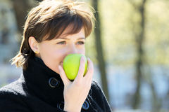 Cute woman in park with apple Royalty Free Stock Photography