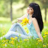 Cute woman in park with dandelions Royalty Free Stock Image