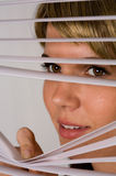 Cute Woman Peeking Through Blinds Stock Photos