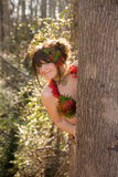 Cute Woman Peeking Out From Behind Tree Royalty Free Stock Photography