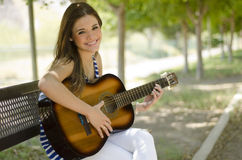 Cute woman playing a guitar. Young beautiful woman playing the guitar in a park bench Stock Photography