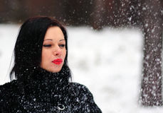 Cute  woman playing with snow in fur coat outdoors Royalty Free Stock Photos
