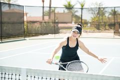 Cute woman playing tennis. Pretty young hispanic female tennis player playing a game on court Stock Image