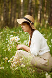 Cute woman plucks daisies on a meadow Stock Photo