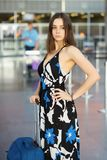 Cute woman posing in the airport. Next to a suitcase dressed in a long dress royalty free stock image