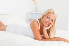 Cute woman posing on her bed Stock Images