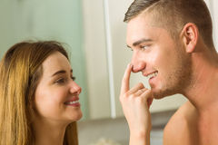 Cute woman putting cream on boyfriends nose Stock Photos