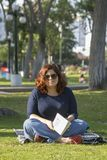 Cute woman reading in the park royalty free stock photography