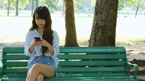 Cute woman is reading pleasant text message on mobile phone while sitting in the park in warm spring day. stock video