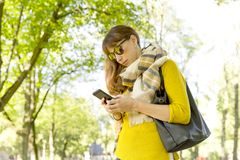 Cute woman is reading pleasant text message on mobile phone while taking a walk in the park in warm fall day Royalty Free Stock Photo