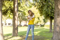 Cute woman is reading pleasant text message on mobile phone while taking a walk in the park in warm fall day Stock Photo