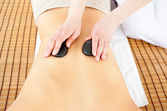 Cute woman receiving back massage with hot stones Royalty Free Stock Photography