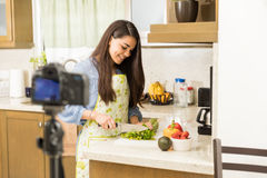 Cute woman recording food vlog. Pretty young female blogger recording a video and cooking a dish for her food vlog Royalty Free Stock Photos