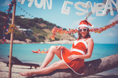 Cute woman in red dress, sunglasses and santa hat sitting on palm tree at exotic tropical beach. Holiday concept for New Royalty Free Stock Image