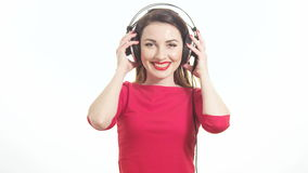 Cute woman in red listening to the music takes off big headphones and winking to the camera smiling isolated on white background stock footage