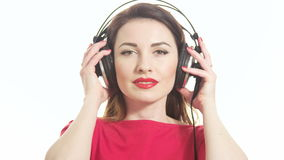Cute woman in red listening to the music takes off big headphones and winking to the camera smiling isolated on white background stock video